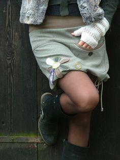 Sukně se sedlem, kapsou a květem Sukně střižená do A, v pase všitá do nápletu, v délce je tunýlek se šňůrkou na stažení do balónku. Sukně má sedlo, do jehož švu je všitá kapsa. Předí díl zdobí aplikace květu s ruční vyšívkou. Tato sukně již má svoji majitelku, napište mi své míry a ušiju Vám novou. V detailech se bude mírně lišit.