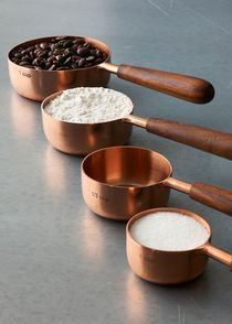 A cup of love, a dash of good tidings – cooking with beautiful kitchen tools makes life so much better. These handcrafted stainless steel and copper measuring cups feature sheesham wood handles for a firm and sturdy grip. The measurements are stamped into the side of the cup, ensuring they'll never fade or wear. Bake up something wonderful in your own kitchen, or give them as a thoughtful holiday or housewarming gift.   Set of four measuring cups – one each of 1/4 cup, 1/3 cup, 1/2 cup…