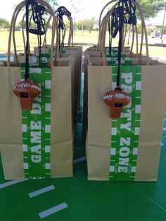 """Our goody bags... So this was really easy... the """"Game Zone"""" wrap was on clearance at Target for something like 10 cents after Superbowl. I just wrapped it around the bags. Also used it for the water bottle labels. Perfect! I filled the bags with football necklaces, mini footballs and other football items."""