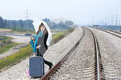 Young woman with a suitcase and umbrella on the railroad. Ready to leave
