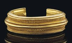 A CELTIC SOLID GOLD BRACELET  IRON AGE, CIRCA 1000 B.C.  With central ridge flanked on each side by a shorter, sharper ridge, and then a line of 'cones', with a line of small, square piercings on either side, the outer edges each with another triple set of ridges, the ridges, cones and piercings extending right along the extent of the bracelet, with no distinct terminals, the interior surface with central longitudinal groove, flanked by a double row of small, square piercings