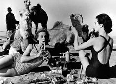 Models Tatiana and Marie Rose picnic with camels in Morocco, 1958. Photo by William Klein.