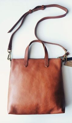 A wrinkled leather Madewell handbag in a timeless, mid-sized profile. Brassy hardware lends low-key shine. Top zip and twill-lined, 2-pocket interior. Top strap handles and optional, adjustable shoulder strap.