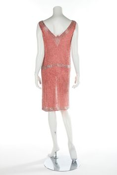 A salmon-pink muslin flapper dress, circa 1928. labelled 'Made in France', entirely covered in silver bugle beads, with beaded flowers in V-shape to front bodice and th