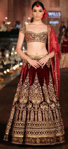 A bridal wine-velvet lehenga set with floral embroidery displayed at the WLIFW 2015 event.