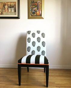 Parson's dining room chair with wooden legs re-stained in Ebony and upholstered with durable black and white material, orange trim and two gold decorative nails.
