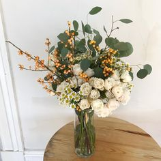 flower arrangement made with spray roses, chamomile, ilex berries and eucalyptus