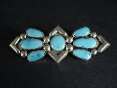 """Worn as a pin at any angle, this gorgeous 7-stone turquoise bow design will get noticed! Large silver beads and silver arrows separate and accent these bright, beautiful stones! The artist wanted to ensure it can also be enjoyed as a pendant, and added the two silver rings with 1/8"""" openings. 