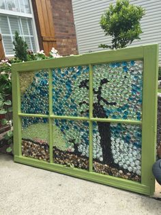 Get the stained glass look, by covering an old window frame in colorful glass marbles
