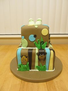 Jungle Safari Baby Shower Cake - Jungle themed baby shower, gumpaste baby shoes on top by request.  Lions, giraffes and monkeys.