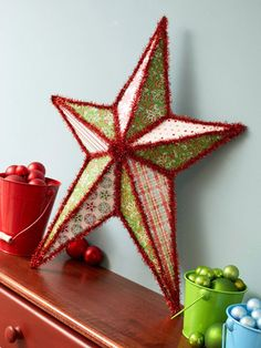 embellish a metal star with scrapbook papers and tinsel trim - trace star pints for the patterns and use a glue stick to adhere papers. hot-glue trim to frame and accent the star