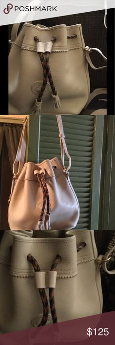 "Dooney and Bourke Teton leather drawstring bag Dooney n Bourke Teton vintage all weather leather drawstring bag B6881917 Beautiful has 3 tiny marks in front under tassel  hides it has metal duck hang tag lovely 13""adjustable straps crime color raw leather inside Dooney & Bourke Bags Hobos"