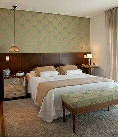 Neste quarto de 11 m², projetado pela designer de interiores Patricia K Pasquini, a estampa utilizada no papel de parede se repete no banco em frente à cama. A cabeceira foi feita com placas de couro natural.