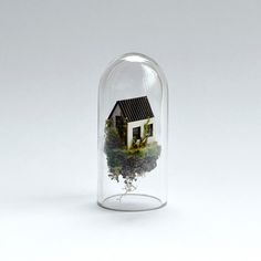 Dutch artist Rosa de Jong constructs worlds inside slender glass test tubes—each complete with micro-sized buildings, teeny tiny trees, and other structures inhabitable by nothing larger than an ant. Comparable to a ship in a bottle, the little houses are made of cardboard while the test tube's environment is made of objects de Jong finds outdoors—sticks brought in by her cat, sand from the Monument Valley, and rocks from the campsites of the Caribbean island of Curacao. At a glance, de…