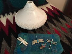 Dragonflies! White clay pottery by Pahponee, sterling silver dragonfly pins and a pink shell Zuni dragonfly carving adorn this end table.