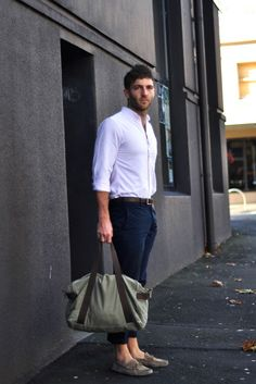 Shop this look on Lookastic:  https://lookastic.com/men/looks/dress-shirt-chinos-boat-shoes-duffle-bag-belt/11232  — Grey Suede Boat Shoes  — Olive Canvas Duffle Bag  — Navy Chinos  — Dark Brown Leather Belt  — White Dress Shirt