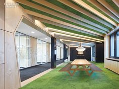 Architects Channel Vibrant City Parks to Create the Perfect Indoor Work Environment | Linoleum protects the benches of a custom birch picnic-style table in the lounge. #interiordesign #design #interiordesignmagazine #projects #officespaces
