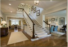 As guests enter the home, they arrive in the elegant foyer, with its impressive staircase, intricate woodwork and wide-plank hardwood floors.  The living room, with built-in bookshelves and beautiful fireplace, is located on the right.  The great room appears straight ahead, with a wall of floor-to-ceiling windows.