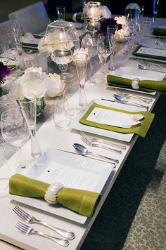 Lime green, hemstitched dinner napkins styled for the men and women in attendance, add color to a crisp white dinner table.