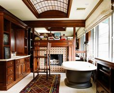 Traditional gentleman's master bathroom with a cast iron tub & walnut cabinetry by Susan Cohen