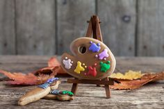 Homemade gingerbread cookies in the form of a palette with paint - Homemade gingerbread cookies in the form of a palette with paint and brushes on the wooden table. Space for text and selective focus