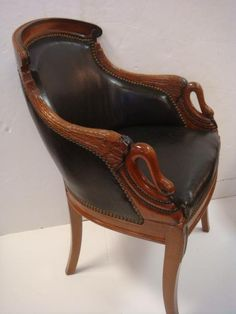 "Petite Gondola Chair with Swan Neck Arm Terminals: Elegantly Curved Crest Rail w/Scroll Ends Down Swept Arms w.Feather Carving. Swans Neck Uprights Accented w/Brad Trim. Larger Brads Surrounding Leather Back & Seat, Saber Legs. A Cat Liked This Chair as Evidenced by Scratches to Leather. Wood Work Beautifully Detailed & Finished. 33"" To Back. (200-300)"
