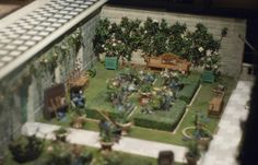 Garden of Queen Mary's Doll House, complete with tiny gardening tools a hedged garden and espaliered trees