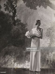 Daphne de Levis Prizer holding a bouquet of narcissi and looking the side, a mural behind her, wearing a white macedonia crepe gown, with a corsage of narcissi at the decolletage, by Lucien Lelong.