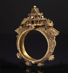 China | Bracelet shrine articulated in gold filigree. Hongzhi Emperor (1470-1505) | Articulated bracelet filigree gold shrine surmounted by a pagoda set of pearls, a phoenix affixed on each side of the building, the body decorated with ruby bracelet shape cabochon bezel-set. Inside, Hongzhi mark and dated June 1488.