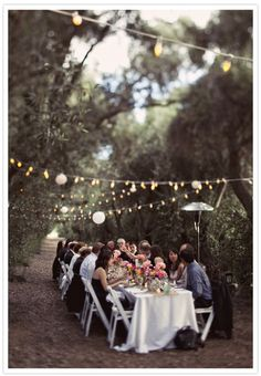 Rustic Dinner outdoors with cafe lights strung from tree to tree