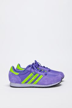 Classic sneaker from Adidas Originals. Part of the Adi's Archive line. Purple upper in suede and nylon with contrast neon green stripes and heel tab. Tone on tone ghilly lacing and hefty tongue. Partly leather lined. All sits on a white shock absorbing mid sole. Extra set of laces included.