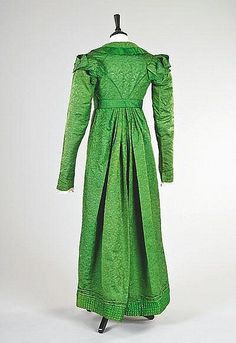 An emerald green figured silk pelisse robe, circa 1815-20...pelisse – An overdress or coat dress, the pelisse fit relatively close to the figure (though not tight) and was styled along the same high-waisted lines as the dress of the day. Pelisses were often lined or edged with fur and, in fashionable circles, more or less replaced the fur-lined cloaks of the earlier periods