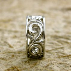 14K White Gold Swirly Wedding Band 8mm Wide with Glossy Finish and Large Scroll Work. $810.00, via Etsy.