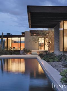 at night ample use of glass gives the house a lantern like quality with light from the living room reflecting off the poolfabricated by phoenician pool - Desert Home Exterior Designs