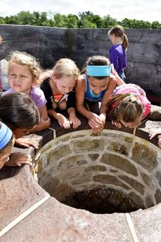 A group of children view the top of the blast furnace during a tour of the Saugus Iron Works.