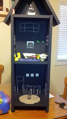 Chalk board Paint on recycled shelf = new doll house.  Champagn caps/ chairs and table.   Corks/Altoid tins  Chalk windows