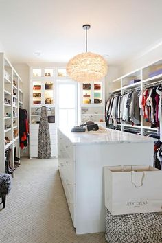 Beautifully designed walk-in closet is every fashionista's dream as it's equipped with a white island fitted with jewelry drawers and a white marble countertop illuminated by a white feather chandelier.