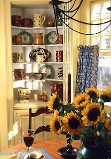 A built-in cabinet, original to the house, dominates a corner of the keeping room. The glass panel door has been left open to reveal a beautiful collection of 18th- and 19th-century majolica, jaspé, and faïence platters, milk pitchers, wine jugs, and mustard pots.