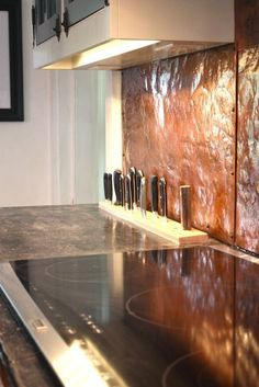 hammered copper backsplash and built-in knife holder - amazing knife storage!