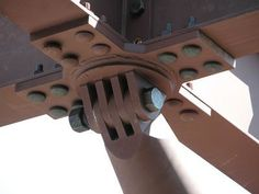 Two types of bolts are used on the connector. TC bolts are used to attach the X plate to the beams. These are chosen for their clean profile. A larger high strength steel bolt with a hex head is used in the connector. We can see that multiple shear planes are developed on this bolt as a result of the large number of plates. Essentially this is a lapped joint.