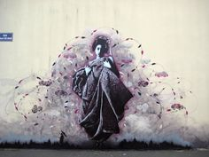 Stunning Geisha Street Art by Fin Dac. This was painted on the streets of Brest, France. The geisha is full of emotion, and is painted in varying shades of pinks and grays.
