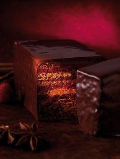 Pierre Hermé. Sous un enrobage gourmand au chocolat noir se cache un biscuit pain d'épices (cannelle, clous de girofle, badiane, vanille) parfumé à l'orange, garni d'une confiture de framboises pépins maison.  Les épices se fondent dans un ensemble harmonieux, agrémenté du goût fruité et de l'acidité de la framboise.  Et le palais en redemande...  Cake Pain d'Epices & Framboise