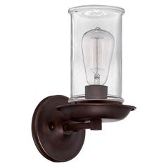 "This rustic clear 1 light wall sconce pairs well with industrial or casual modern decor with its clear glass cylinder hurricane and aged bronze finish. 100 watts medium socket. (11.5""Hx6.13""Wx7.5""D)3.5 lbs.5"" backplate. Transitional Wall Sconces, Contemporary Wall Sconces, Transitional Lighting, Exterior Wall Light, Exterior Lighting, Rustic Lighting, Wall Sconce Lighting, Bathroom Lighting, Direct Lighting"