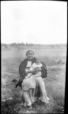 Outside portrait of Viola Chihuahua (Chiricahua Apache) posing with baby Agnes in her arms. 1916
