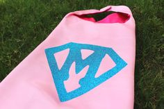 Super girl Cape, girls superhero cape, pink cape with hot pink liner and aqua supergirl symbol    This Superhero Cape is a perfect birthday gift! You also have the option to a name. Below are links for you to select a coordinating mask and wristbands to add to your shopping cart, it is not included. My shop is setup to combine shipping when you order the accessories. :)    ***MASK SOLD SEPARATELY*** (please see links below)    The material is very soft and light which creates the real…