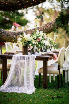 Hawaii wedding, outdoor reception, farm table, gauzy lace runner, pink linens, twinkling lights, tree trunk planters // Chris J. Evans Photography