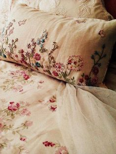 Soft bed linen with mauve and plum accents.