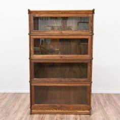 This rustic lawyers bookcase is featured in a solid wood with a dark oak finish. This bookshelf cabinet is in great condition with 4 shelves, 4 lift up clear glass doors and carved trim. Timeless storage piece perfect for displaying books and knick knacks! #traditional #storage #bookcase&shelving #sandiegovintage #vintagefurniture