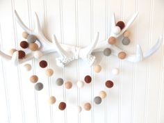 Woodland Garland, Neutral Nursery Decor, Baby Boy Room, Natural, Bunting, Pom Pom Garland, Gender Neutral, Khaki, Flax, Ecru, Taupe, Brown from theblushingfig.com. starting at $14.75