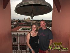 Couple at the top of the Granada Church in front of the bell with a beautiful view at their back of the granada city in Nicaragua... See more at: https://www.costaricamonkeytours.com/costarica-travelguide/things-to-do/